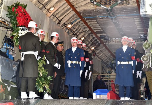 In this image provided by the Turkish Military, Turkish honour guards stand after they placed the coffin of Russian pilot Lt. Col. Oleg Peshkov inside a Russian Air Force transport plane at Esenboga Airport in Ankara, Turkey, Monday, Nov. 30, 2015. Early