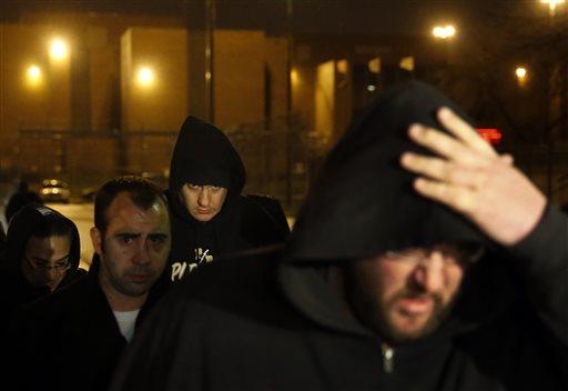 Chicago Police Officer Jason Van Dyke, back middle, leaves the Cook County Jail after posting bond on Monday, Nov. 30, 2015, in Chicago. (AP Photo/Charles Rex Arbogast)