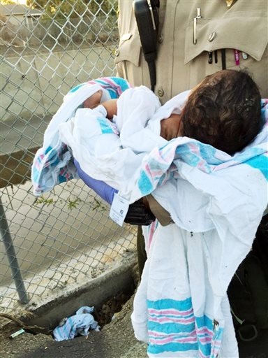 Friday, Nov. 27, 2015 file photo from the Los Angeles County Sheriff's Department shows Deputy Adam Collette holding an infant girl where she was found abandoned under asphalt near a bike path in Compton, Calif. (LA Cnty Sheriff's Department via AP, File)
