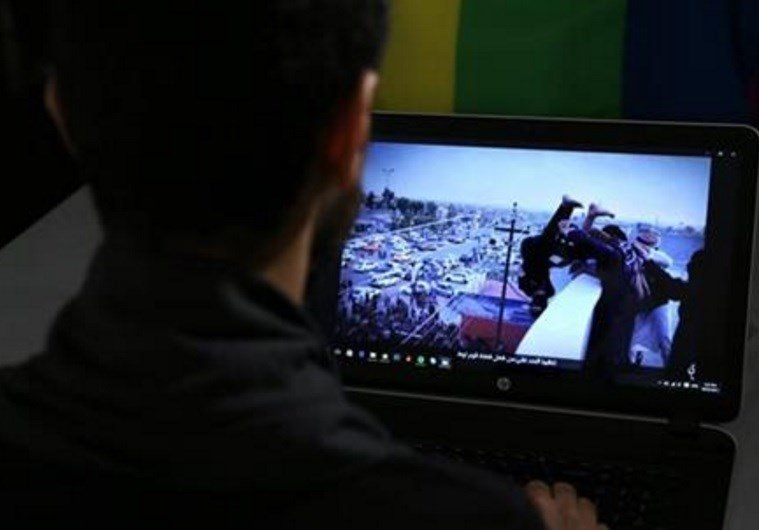 GRAPHIC CONTENT - In this Oct. 22, 2015, photo, Daniel Halaby, a gay Syrian living in southern Turkey, shows a photo from his laptop of Islamic State group militants throwing a man off a roof for allegedly violating the extremists' ban on homosexuality.
