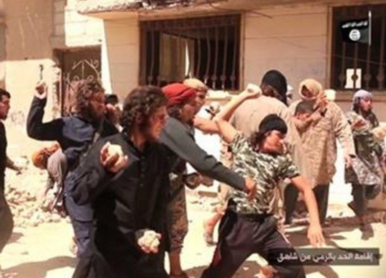 IS militants stone a man accused of violating the extremists' ban on homosexuality after they threw him from a roof in the city of Homs, Syria. AP