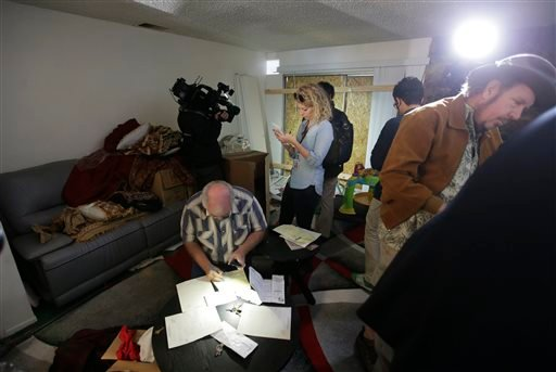 Members of the media crowd into the living room of an apartment in Redlands, Calif., shared by San Bernardino shooting rampage suspects Syed Farook and his wife, Tashfeen Malik, Friday, Dec. 4, 2015. (AP Photo/Chris Carlson)