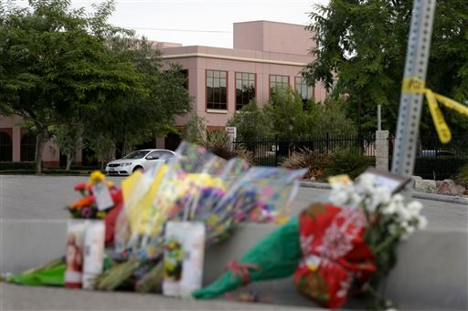 Flowers are placed near the building, top center, where Wednesday's shooting rampage took place at the Inland Regional Center, Sunday, Dec. 6, 2015, in San Bernardino, Calif. The FBI said it's investigating the massacre in San Bernardino, California, that