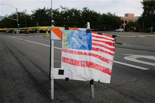 A hand-painted American flag is seen near the building, top right, where Wednesday's shooting rampage took place, at the Inland Regional Center, Sunday, Dec. 6, 2015, in San Bernardino, Calif. The FBI said it's investigating the massacre in San Bernardino