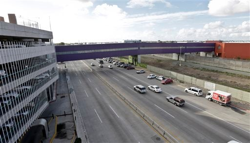 In this Wednesday, Nov. 25, 2015 photo taken in Tijuana, Mexico, vehicles pass under a walking bridge that connects the new Cross Border Xpress air terminal in San Diego, right, to the Tijuana International Airport, left.