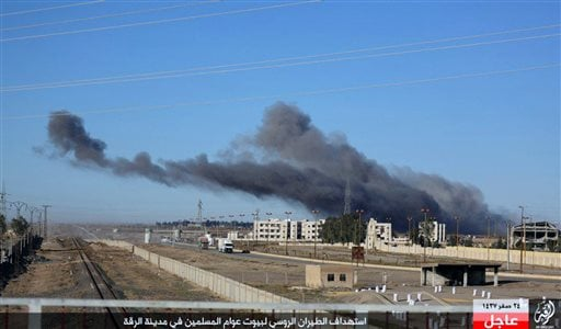 This image posted online Sunday, Dec. 6, 2015, by supporters of the Islamic State militant group on an anonymous photo sharing website, shows smoke rising in the aftermath of an airstrike that targeted areas in Raqqa, Syria. The photo bears the watermark