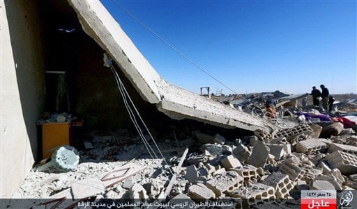 This image posted online Sunday, Dec. 6, 2015, by supporters of the Islamic State militant group on an anonymous photo sharing website, shows Syrians inspecting a damaged building in the aftermath of an airstrike that targeted areas in Raqqa, Syria. The p