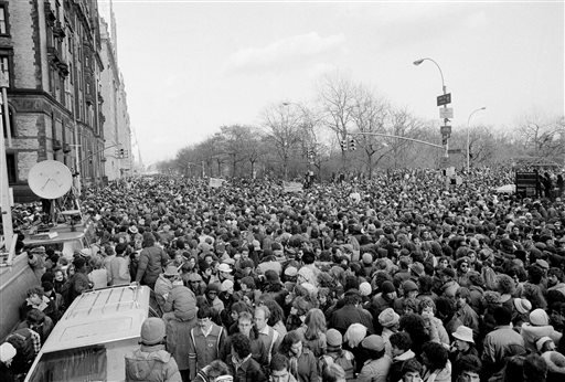 In this Dec. 14, 1980, file photo, people jam the street at Central Park West and 72nd Street in New York, just outside the Dakota apartment house where John Lennon lived, after leaving a memorial service held at the bandshell in Central Park.