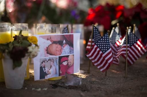 A photo collage of Robert Adams, one of the victims in the San Bernardino shootings at the Inland Regional Center, is placed next to small American flags at a makeshift memorial, Tuesday, Dec. 8, 2015, in San Bernardino, Calif. Just days before Syed Faroo