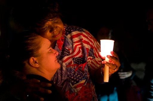 Lisa Hamons, front, a social worker for San Bernardino County, is hugged by Yolanda Richardson during a candlelight vigil for shooting victims on Monday, Dec. 7, 2015, in San Bernardino, Calif. The husband and wife who opened fire on a social services cen