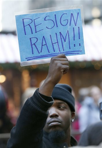 A protester holds ups a sign calling for the resignation of Chicago Mayor Rahm Emanuel during a protest march calling for the mayor and Cook County State's Attorney Anita Alvarez to resign Wednesday, Dec. 9, 2015, in Chicago. (AP Photo/Charles Rex Arbogas