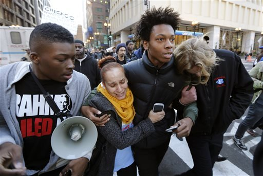 Lamon Reccord, second from right, is reunited with fellow protesters after being released by Chicago police officers during a march calling for Chicago Mayor Rahm Emanuel and Cook County State's Attorney Anita Alvarez to resign Wednesday, Dec. 9, 2015, in