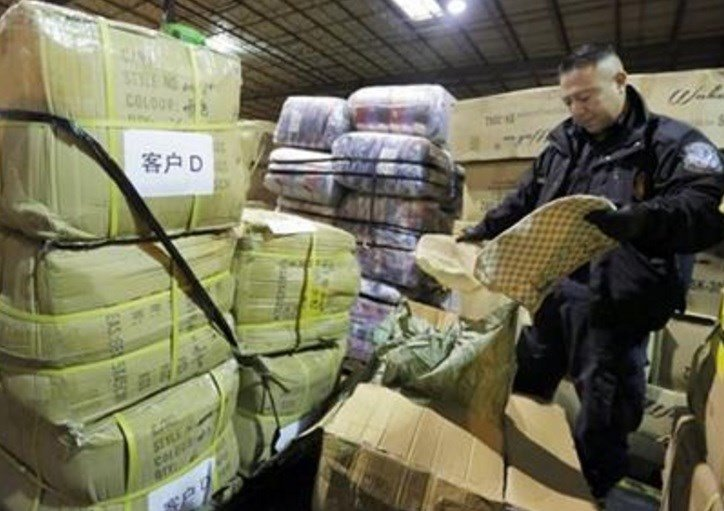 In this Wednesday, Oct. 28, 2015 photo, U.S. Customs and Border Protection officer John Montalvo opens a shipment of counterfeit Louis Vuitton bags at H&M Terminals Transport Inc. warehouse in Kearney, N.J. AP