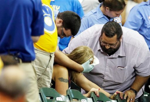 In this July 6, 2015, file photo, a fan is helped after being hit by a foul ball during the ninth inning of a baseball game between the Milwaukee Brewers and the Atlanta Braves in Milwaukee.