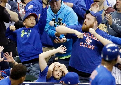 In this Oct. 2, 2015, file photo, fans go after a foul ball hit by Chicago Cubs' Dexter Fowler during the third inning of a baseball game against the Milwaukee Brewers, in Milwaukee.