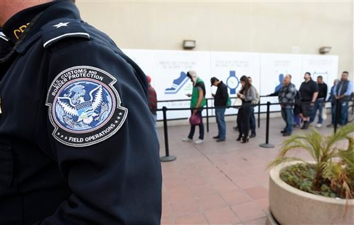 Pedestrians crossing from Mexico into the United States at the Otay Mesa Port of Entry wait in line Thursday, Dec. 10, 2015, in San Diego.