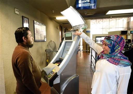 Contractor Sabira Dewji, right, helps a pedestrian crossing from Mexico into the United States at the Otay Mesa Port of Entry have his facial features and eyes scanned at a biometric kiosk Thursday, Dec. 10, 2015, in San Diego.
