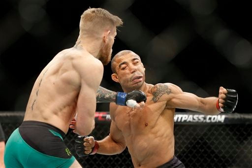 Conor McGregor, left, fights Jose Aldo during a featherweight championship mixed martial arts bout at UFC 194, Saturday, Dec. 12, 2015, in Las Vegas.