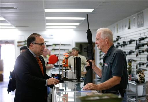 In this Dec. 9, 2015, photo, sales associate Mike Conway, right, shows Paul Angulo a semiautomatic rifle at Bullseye Sport gun shop in Riverside, Calif. The massacre at Sandy Hook elementary school in which a mentally disturbed young man killed 26 childre