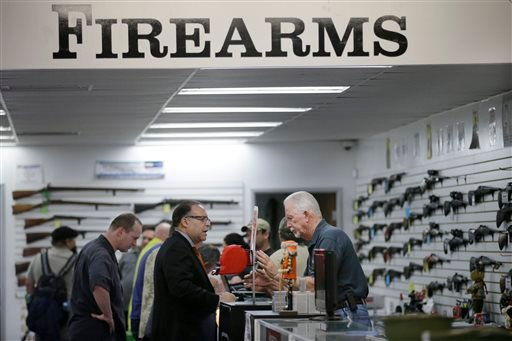 In this Dec. 9, 2015, photo, sales associate Mike Conway, right, shows Paul Angulo a pistol at Bullseye Sport gun shop in Riverside, Calif. The massacre at Sandy Hook elementary school in which a mentally disturbed young man killed 26 children and teacher