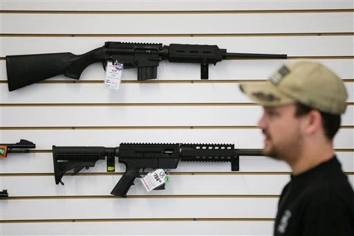 In this Dec. 9, 2015, photo, a sales associate walks past semiautomatic rifles at Bullseye Sport gun shop in Riverside, Calif. The massacre at Sandy Hook elementary school in which a mentally disturbed young man killed 26 children and teachers galvanized