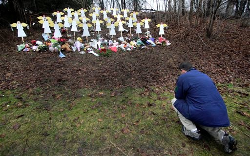 In this Dec. 18, 2012, file photo, Robert Soltis, of Newtown, Conn., pauses after making the sign of the cross at a memorial to Sandy Hook Elementary School shooting victims in Newtown. The massacre in Newtown, in which a mentally troubled young man kille