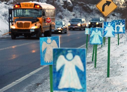 In this Jan. 3, 2013, file photo, a bus traveling from Newtown, Conn., to Monroe stops near 26 angel signs posted along the roadside in Monroe, Conn., on the first day of classes for Sandy Hook Elementary School students since the Dec. 14, 2012, shooting