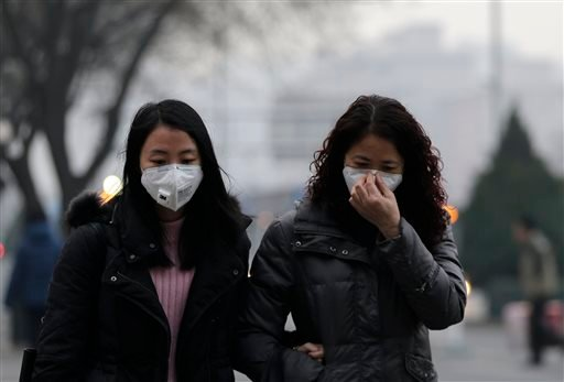 Women wear masks for protection against the pollution as they walk along a street on a polluted day in Beijing, Sunday, Dec. 13, 2015. China's push for a global climate pact is partly because of its own increasingly pressing need to solve serious environm