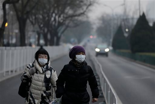 Women wear masks as they walk along a street on a polluted day in Beijing, Sunday, Dec. 13, 2015. China's push for a global climate pact is partly because of its own increasingly pressing need to solve serious environmental problems, observers said Sunday
