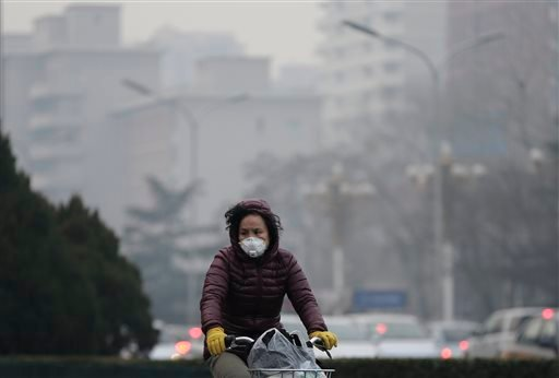 A woman wears a mask as she rides across a road on a polluted day in Beijing, Sunday, Dec. 13, 2015. China's push for a global climate pact is partly because of its own increasingly pressing need to solve serious environmental problems, observers said Sun