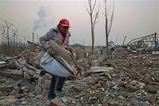 In this Dec. 12, 2015 file photo, a scrap collector gathers materials in a demolished neighborhood near a chimney spewing smoke in Beijing, China. China's push for a global climate pact is partly because of its own increasingly pressing need to solve its