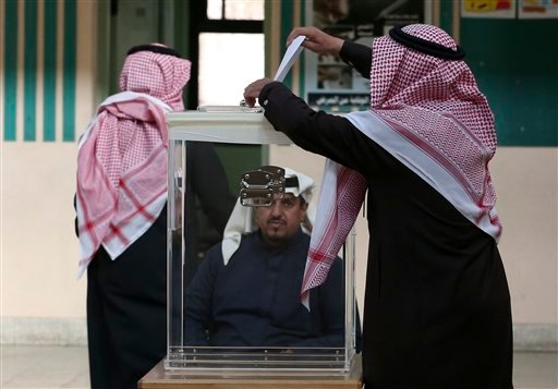 A Saudi man, center, casts his vote at a polling center during the country's municipal elections in Riyadh, Saudi Arabia, Saturday, Dec. 12, 2015. Women across Saudi Arabia marked a historic milestone on Saturday, both voting and running as candidates in