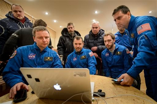 In this photo provided by NASA, members of NASA and the Russian support teams who were unable to fly to the Soyuz TMA-17M landing site due to weather, watch a live video stream of the U.S. space agency's Kjell Lindgren, Russia's Oleg Kononenko and Kimiya