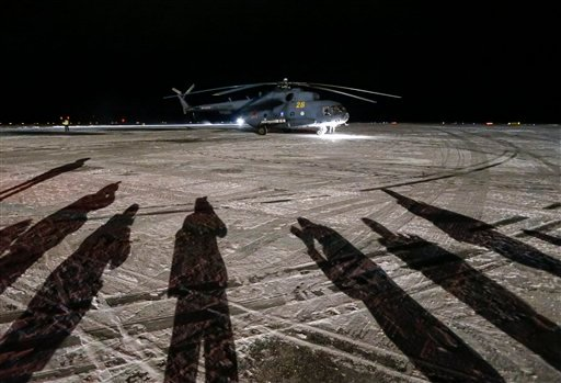 Cameramen cast shadows as they film a helicopter carrying International Space Station crew member Kimiya Yui of Japan on arrival from the landing site to Dzhezkazgan, Kazakhstan, Friday, Dec. 11, 2015. A three-person crew, U.S. space agency's Kjell Lindgr