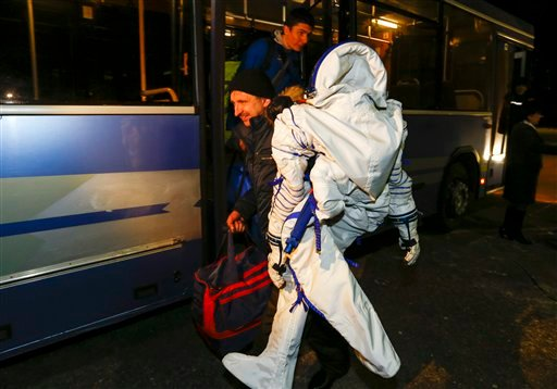 A member of the search and rescue team carries a spacesuit of International Space Station crew member Kimiya Yui of Japan on arrival from the landing site to Dzhezkazgan, Kazakhstan, Friday, Dec. 11, 2015. A three-person crew, U.S. space agency's Kjell Li