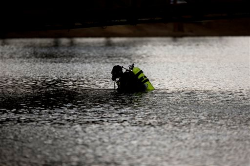 A member of the FBI dive team searches Seccombe Lake Friday, Dec. 11, 2015, in San Bernardino, Calif., for evidence in connection with last week's fatal shooting at Inland Regional Center, The FBI says divers are searching the lake because leads indicate