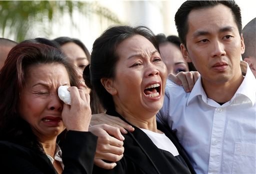 Trung Do Nguyen, right, comforts his mother, Van Thanh Nguyen, at a wake for his sister and her daughter, Tin Nguyen, at the Peek Funeral home in Westminster, Calif., on Friday, Dec. 11, 2015. Nguyen died in the mass shootings in San Bernardino, Calif., l