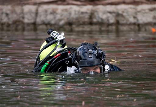 A member of the FBI dive team searches Seccombe Lake, Friday, Dec. 11, 2015, in San Bernardino, Calif., for evidence in connection with last week's fatal shooting at Inland Regional Center, The FBI says divers are searching the lake because leads indicate
