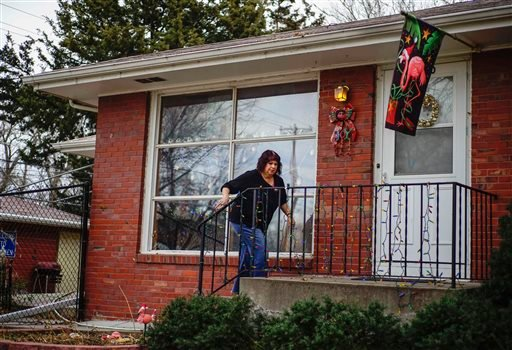 Graphic designer Rayna Collins walks into her home in Lincoln, Neb. Dec. 11, 2015. Rising premiums and shaken faith among insurers have cast a cloud over sign-up season for President Barack Obama's health care law. (AP Photo/Nati Harnik)