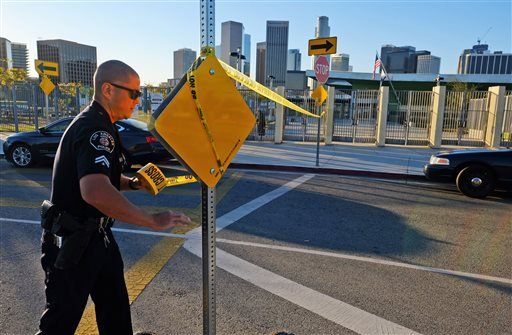 A police officer puts up yellow tape to close the school outside of Edward Roybal High School in Los Angeles, on Tuesday morning, Dec. 15, 2015.