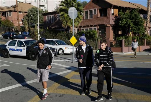 Los Angeles-area students walk to school at the Edward R. Roybal Learning Center in Los Angeles Wednesday, Dec. 16, 2015. Students are heading back to class a day after an emailed threat triggered a shutdown of the vast Los Angeles Unified School District