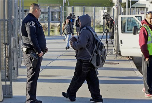 Los Angeles School Police officer Alex Camarillo, left, welcomes area students back to school at the Edward R. Roybal Learning Center in Los Angeles Wednesday, Dec. 16, 2015. Students are heading back to class a day after an emailed threat triggered a shu