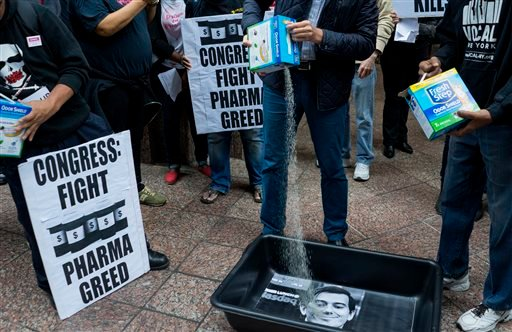 In this Oct. 1, 2015 file photo, AIDS activists pour cat litter on an image of Turing Pharmaceuticals CEO Martin Shkreli in a makeshift cat litter pan during a protest highlighting pharmaceutical drug pricing in New York.