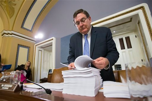 House Rules Committee member Rep. Michael C. Burgess, R-Texas, examines a printout of the $1.1 trillion spending bill to fund the government for the 2016 budget year and extend $680 billion in tax cuts for businesses and individuals, at the Capitol in Was