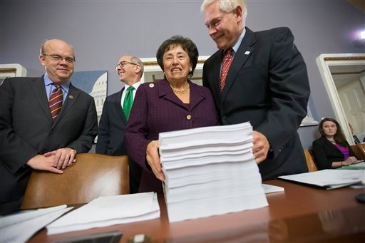 House Rules Committee Chairman Pete Sessions, R-Texas, right, welcomes Rep. Nita Lowey, D-N.Y., the ranking member of the House Appropriations Committee, and Rules Committee member Rep. James P. McGovern, D-Mass., far left, as they gather around a printou