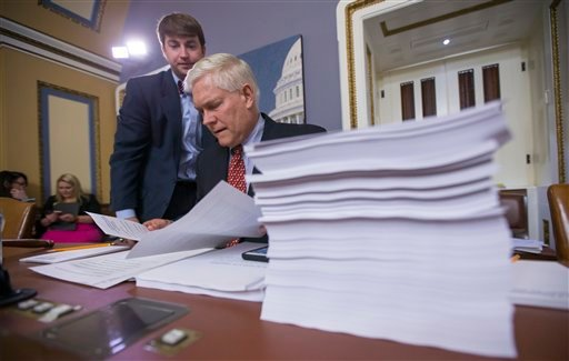 House Rules Committee Chairman Pete Sessions, R-Texas, examines a printout of the $1.1 trillion spending bill to fund the government for the 2016 budget year and extend $680 billion in tax cuts for businesses and individuals, at the Capitol in Washington,
