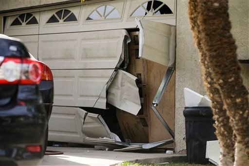 In this Dec. 9, 2015 file photo, a garage door of Enrique Marquez's home is broken in after an FBI raid, in Riverside, Calif. Marquez a former security guard who bought the assault rifles used by his friend in the San Bernardino massacre, was expected to