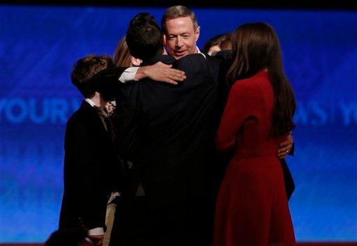 Martin O'Malley is hugged after a Democratic presidential primary debate Saturday, Dec. 19, 2015, at Saint Anselm College in Manchester, N.H. (AP Photo/Jim Cole)