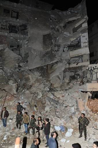 In this photo released Sunday, Dec. 20, 2015, by the Syrian official news agency SANA, Syrian soldiers stand in front of a damaged building where Samir Kantar was believed to be killed along with several others Saturday night in the Damascus suburb of Jar