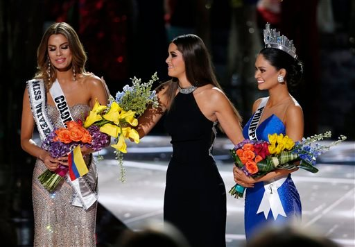 Former Miss Universe Paulina Vega, center, takes away the flowers and sash from Miss Colombia Ariadna Gutierrez, left, before giving them to Miss Philippines Pia Alonzo Wurtzbach, right, at the Miss Universe pageant on Sunday, Dec. 20, 2015, in Las Vegas.